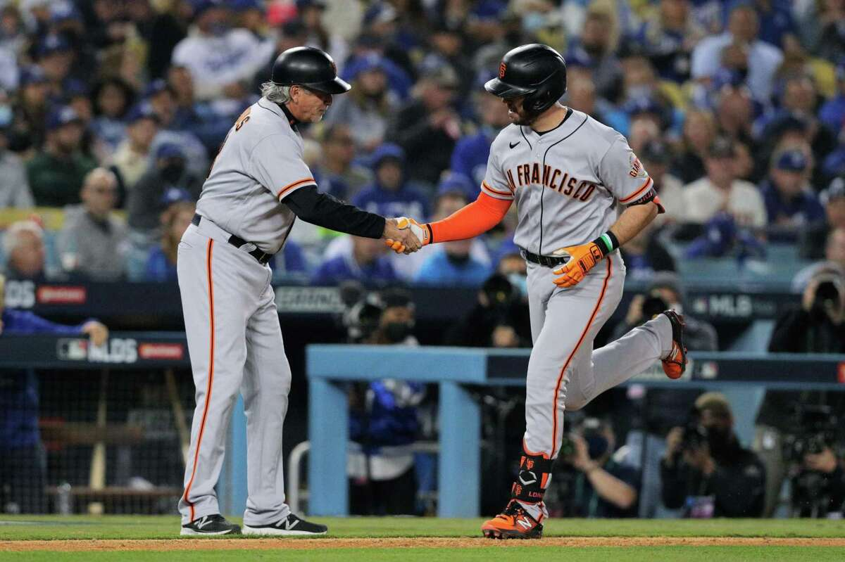 San Francisco Giants Evan Longoria (10), right, is congratulated by third base coach Ron Wotus (23) after Longoria's solo home run during the top of the fifth inning as the San Francisco Giants played the Los Angeles Dodgers in Game 3 of the National League Division Series at Dodger Stadium in Los Angeles, Calif. on Monday, Oct. 11, 2021.