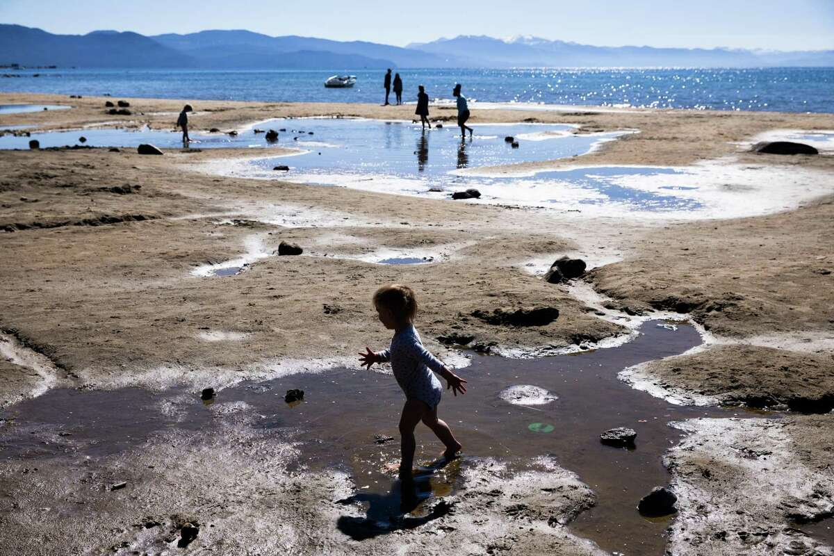 """Kids play on puddles left on exposed lakebed at Kings Beach at Lake Tahoe on Sunday. Drought conditions have left the lake perilously close to becoming """"terminal,"""" where water levels are so low that it can no longer supply its only outflow and water in the lake basin will become stagnant."""