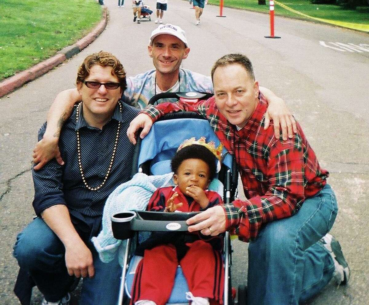 """Kevin Fisher-Paulson (right) with his son Zane, Tim Powers (center) and """"Uncle Jon"""" at the AIDS Walk in 2004."""