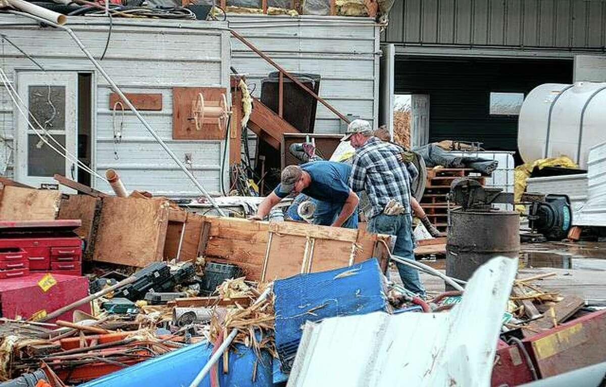 Property owner Scot Wright (left) rummages through items on his farm Monday afternoon after a tornado came through destroying sheds, a silo and farm equipment in Wrights in Greene County.