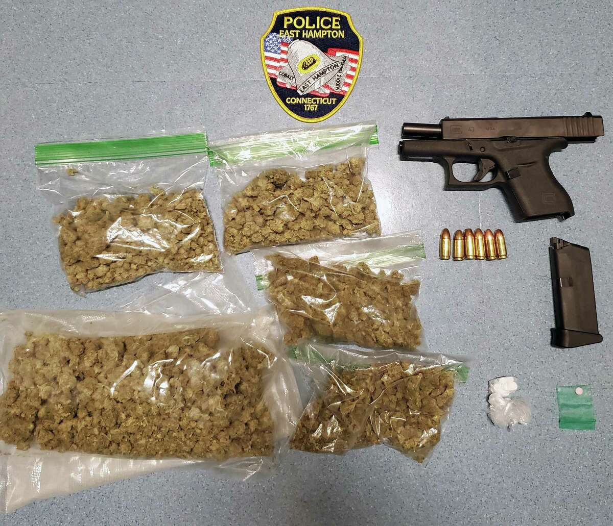 Half a pound of marijuana and a gun with the serial number scratched off were found by officers at the scene of an investigation in East Hampton, Conn., on Oct. 6, 2021, police said. Federal and local authorities continue to try to figure out who owned the gun.