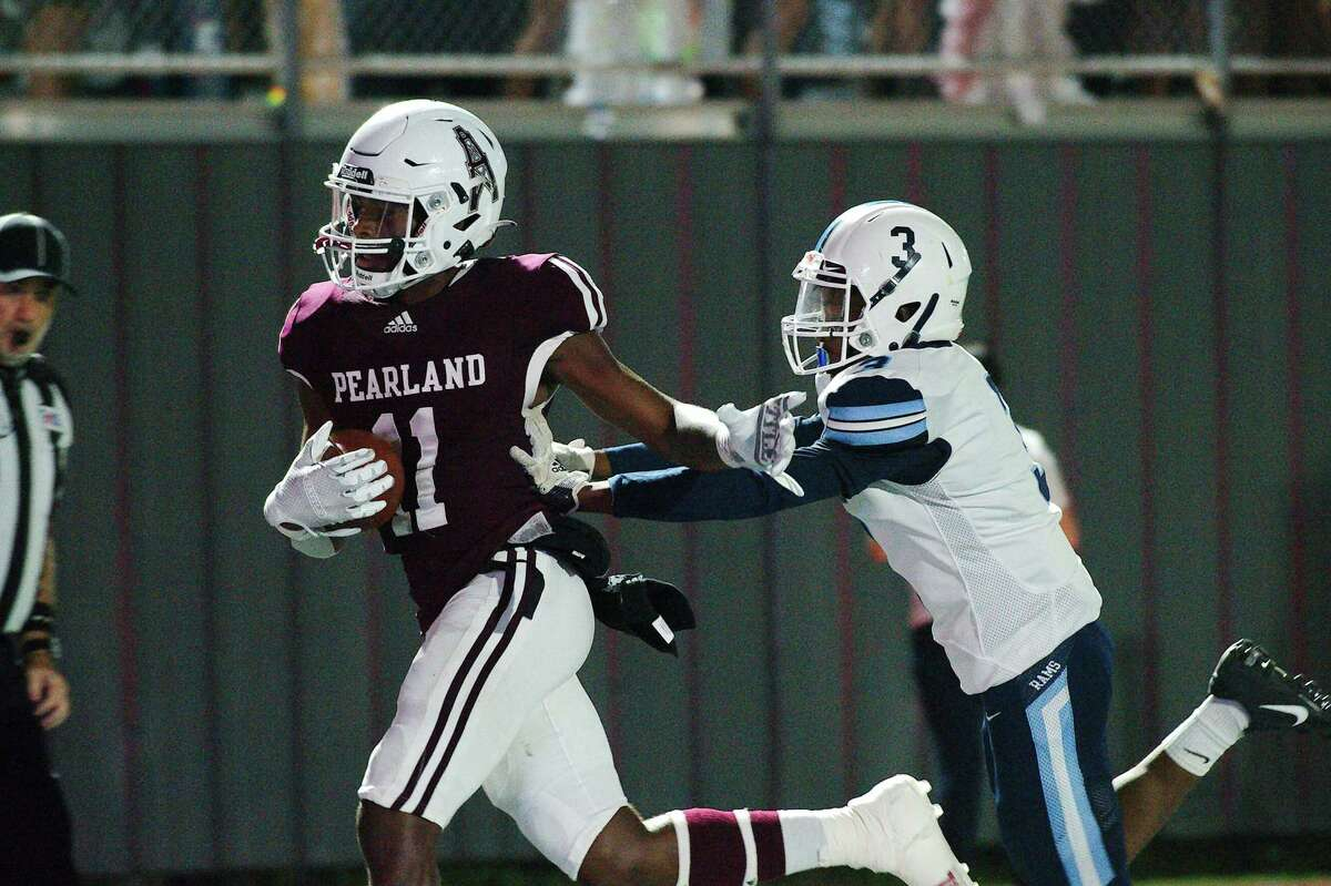Pearland's Patrick Bridges (11) pulls down a pass and sprints into the end zone past Alief Elsik's Jacory Whigham (3) for a touchdown against Alief Elsik Friday at The Rig.