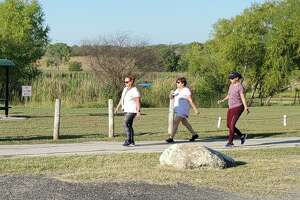 Three women walk a path at Converse North Park while a fisherman tries his luck from a boat on the lake behind. The city's public works department received a TML Municipal Excellence Award for its recent focus on park upgrades and improvements.
