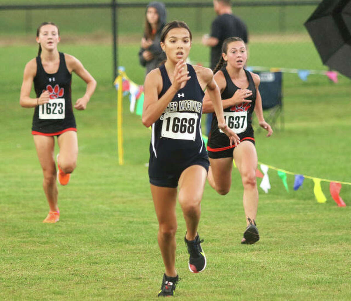 Father McGivney sophomore Kaitlyn Hatley (1668) outruns Edwardsville's Olivia Coll (right) and Emily Nuttall in the final meters before the finish in the Madison County Meet on Oct. 5 at the Bethalto Sports Complex.