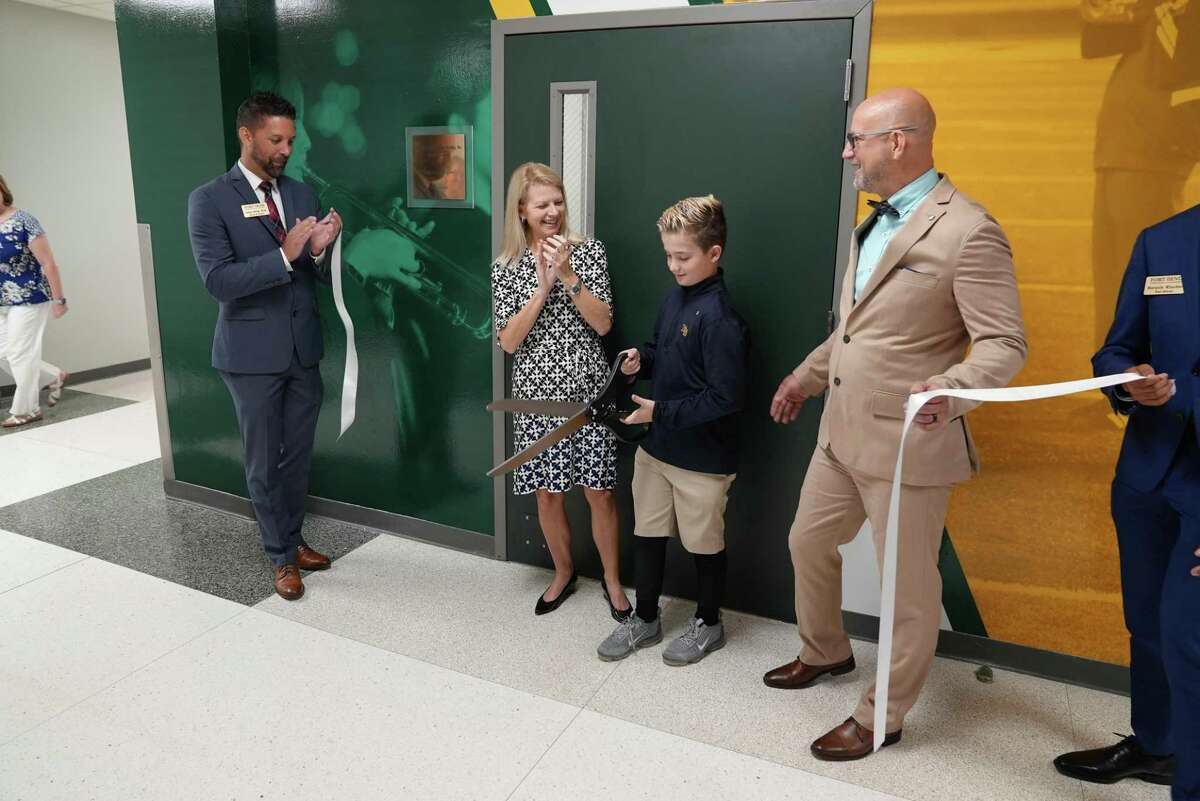 Celebrating the new Edward Anthony Scala Sr. Band Room at Fort Bend Christian Academy, Head of Schools Joshua Gettys, left, and Director of Fine Arts Robert Sanders, right, look on as Board of Trustees Vice President Alicia Scala and her son, Eddie, cut the ribbon on Thursday, Sept. 30.