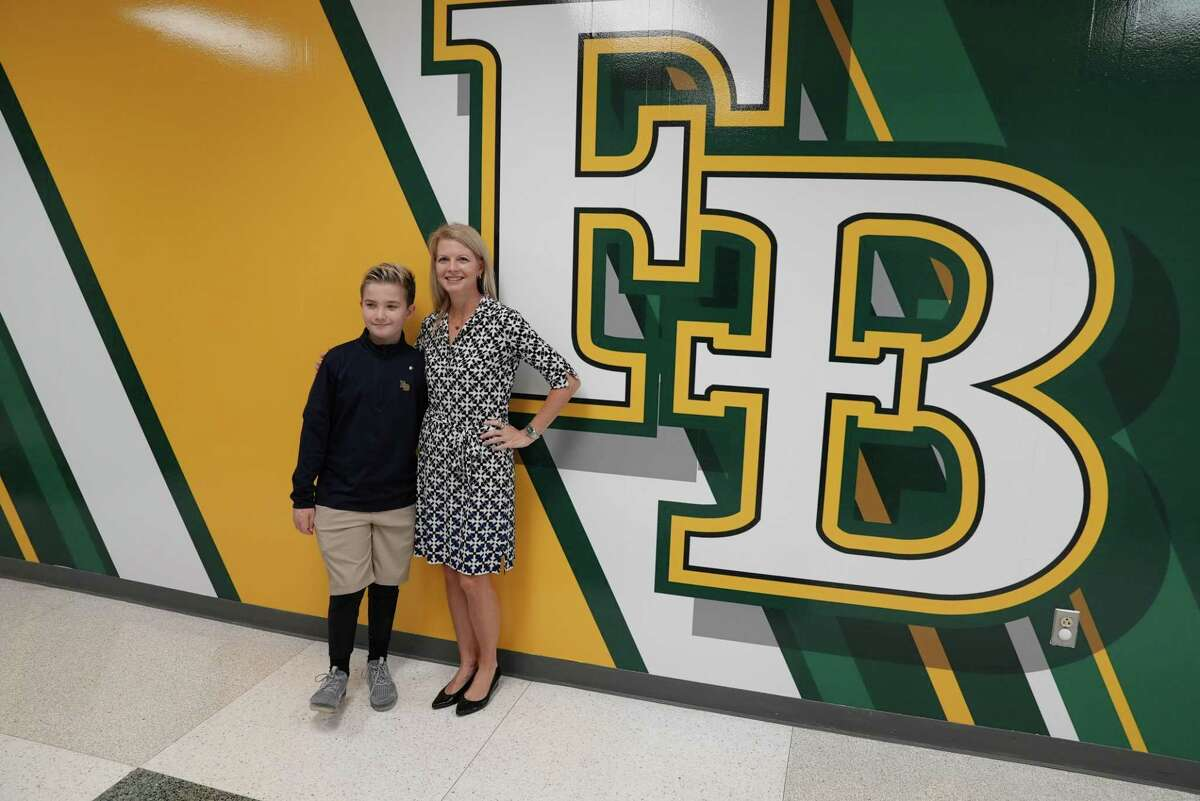 At Fort Bend Christian Academy in Sugar Land, Board of Trustees Vice President Alicia Scala and her son, Eddie, pose on Thursday, Sept. 30, outside the new Edward Anthony Scala Sr. Band Room their donation made possible. The wall graphic was part of the renovation.