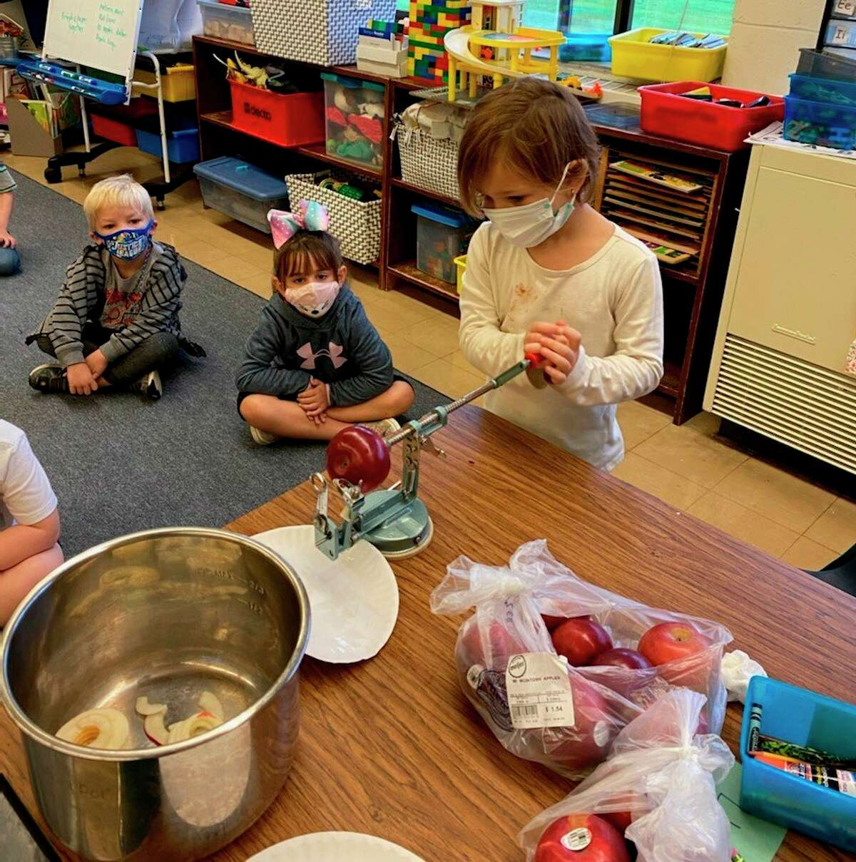 A kindergarten student at Jefferson Elementary peels an apple to make applesauce on Friday. (Courtesy photo)