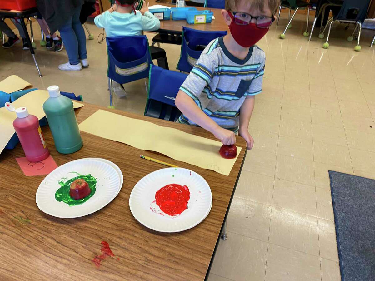 A kindergarten student at Jefferson Elementary marks a sheet of paper with an apple and paint on Friday. (Courtesy photo)