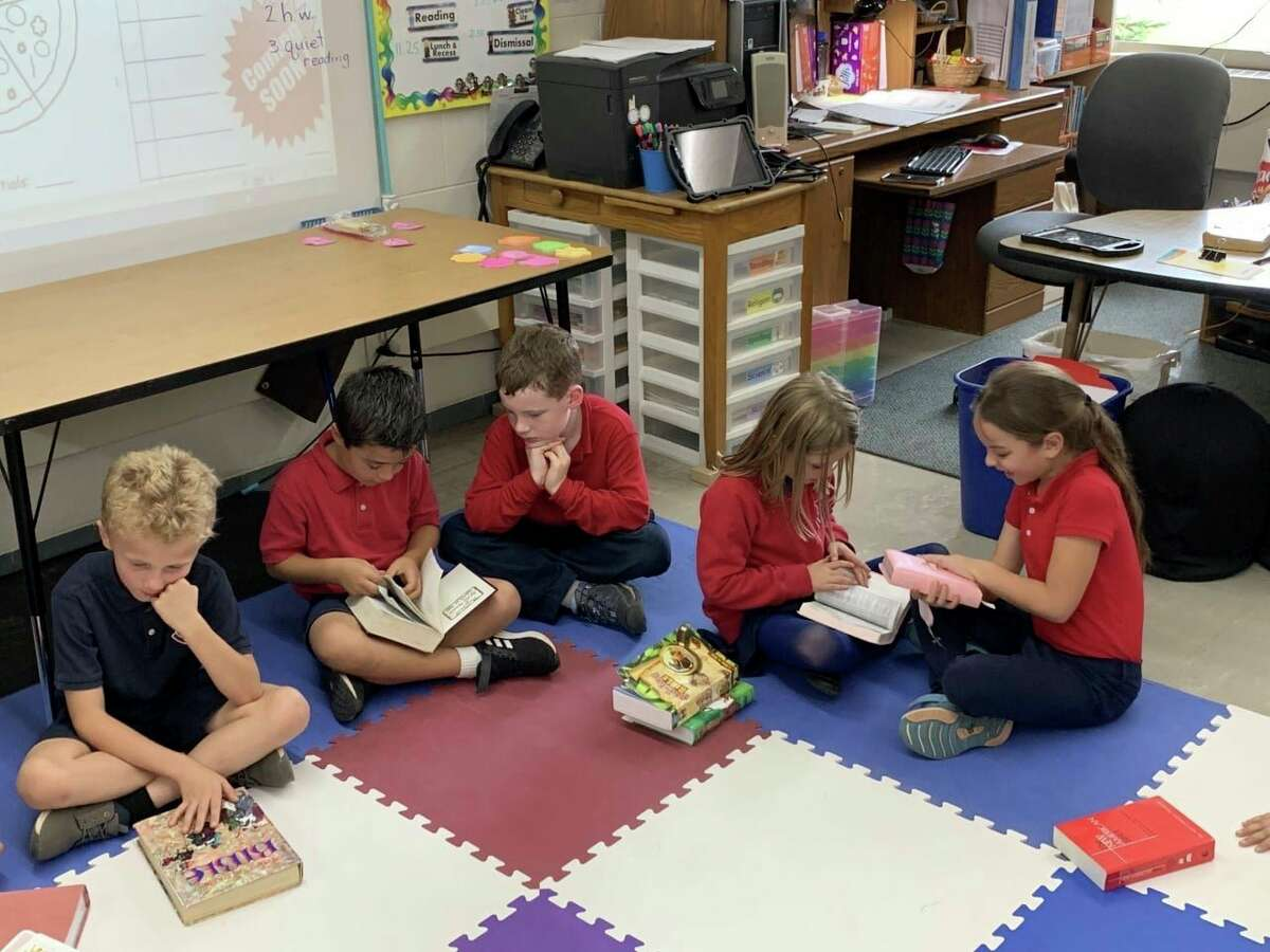 Manistee Catholic Central students in Laura Cameron's second grade class share their Bibles on National Bring Your Bible to School Day. (Courtesy photo)