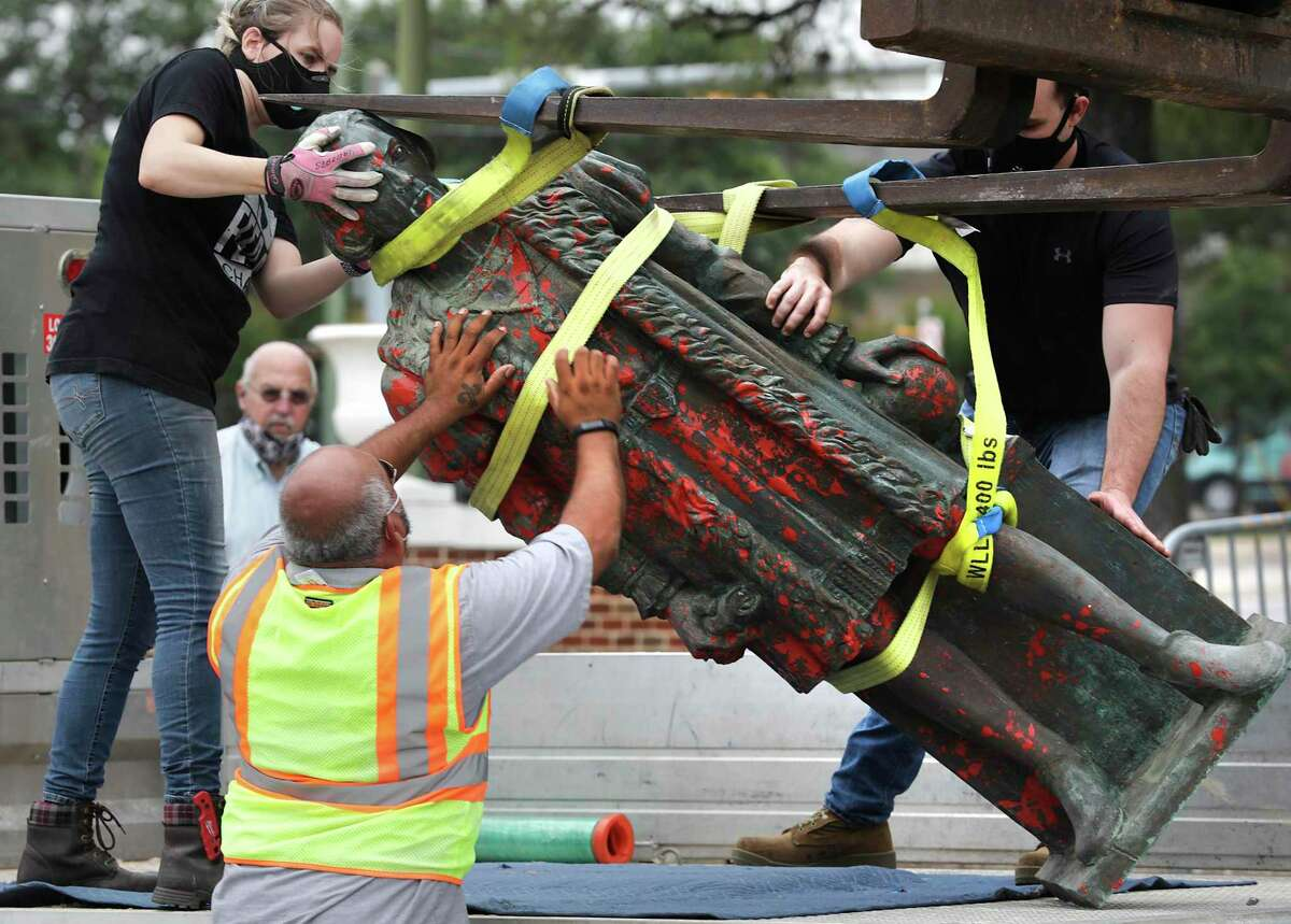 Workers hired by the City of San Antonio, carefully remove the statue of Christopher Columbus from Columbus Park, on July, 1, 2020.