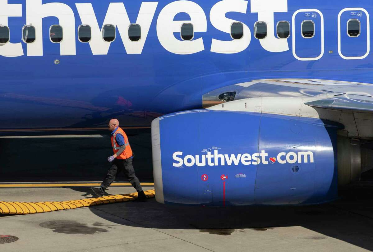 A member of the ground crew sets up equipment after a Southwest airplane landed and pulled up to a gate at Albany International Airport on Tuesday, Oct, 12, 2021 in Albany, N.Y. Southwest's cancellations nationwide over Columbus Day weekend could be a prediction for what Thanksgiving will look like.