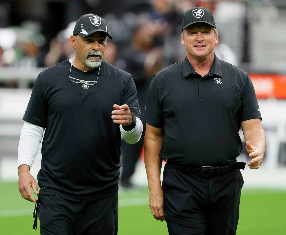 Assistant head coach/special teams coordinator Rich Bisaccia (L) and head coach Jon Gruden of the Las Vegas Raiders talk on the field before their game against the Chicago Bears at Allegiant Stadium.