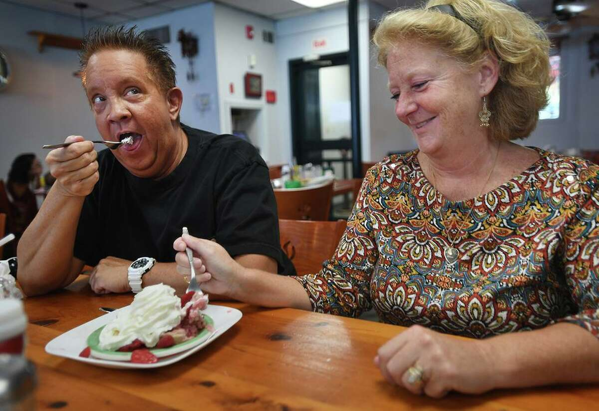 Town employees John O'Connell of Clinton and Sharon Uricchio of Deep River share a strawberry shortcake for dessert at the newly reopened and remodeled The Coffee Break diner in Clinton.