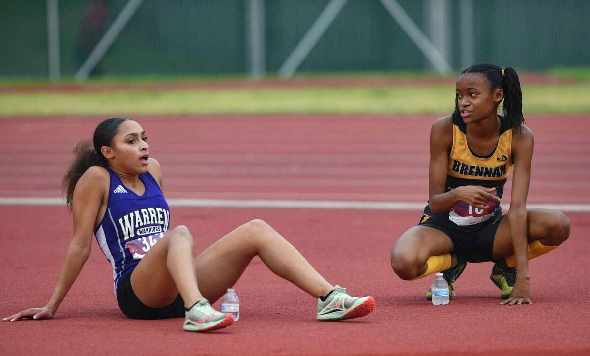 Sanai Robinson, left, of Warren High and Caila Lyons of Brennan converse after finishing first and second in the District 29-6A Cross Country Championships at Gustafson Stadium on Tuesday, Oct. 12, 2021.
