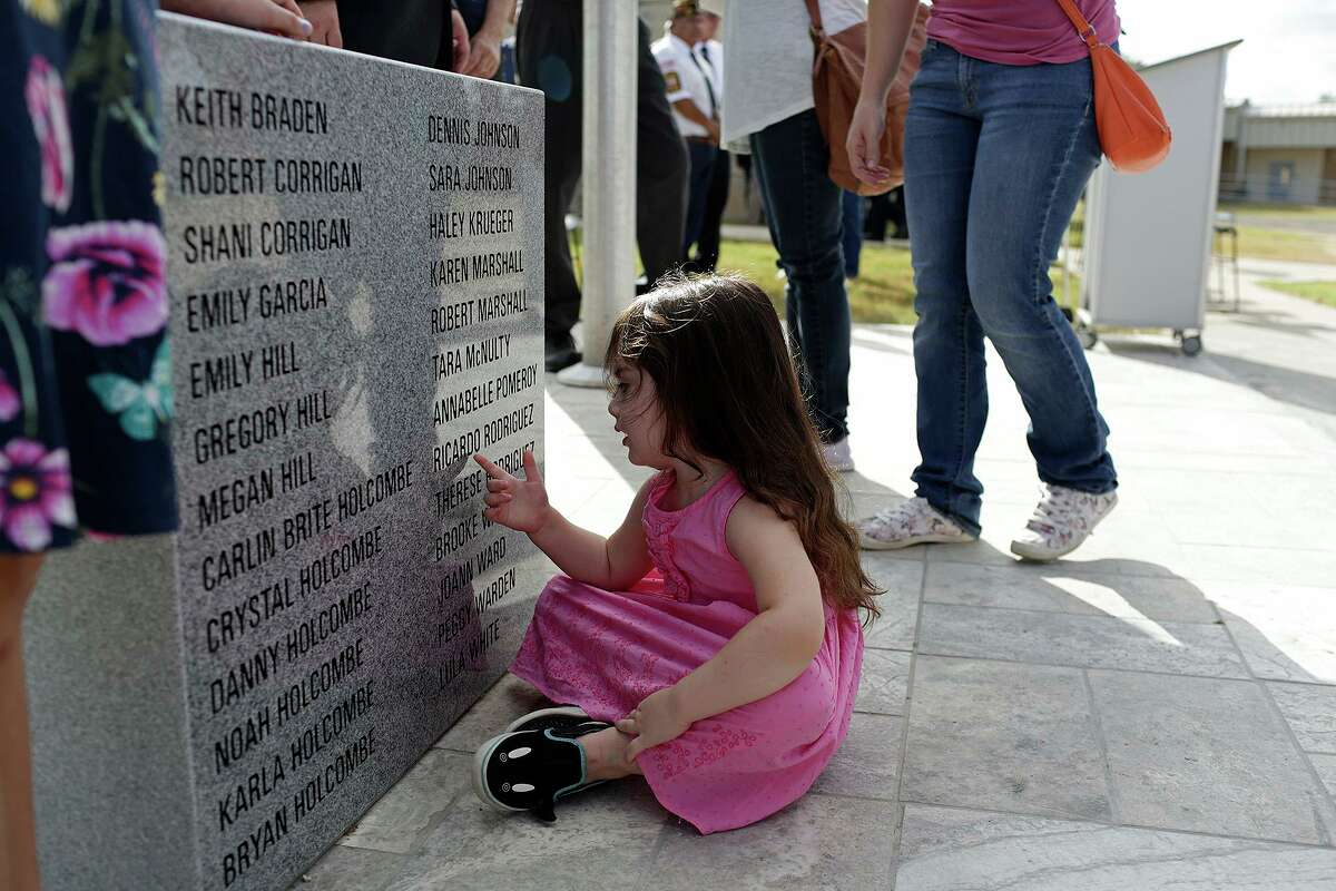 Elene Slavin, 3, a member of the Holcombe family, touches the memorial dedicated to the victims from First Baptist Church of Sutherland Springs, including nine members of her family, at the Wilson County District Court Justice Center in Floresville on Aug. 31, 2018.