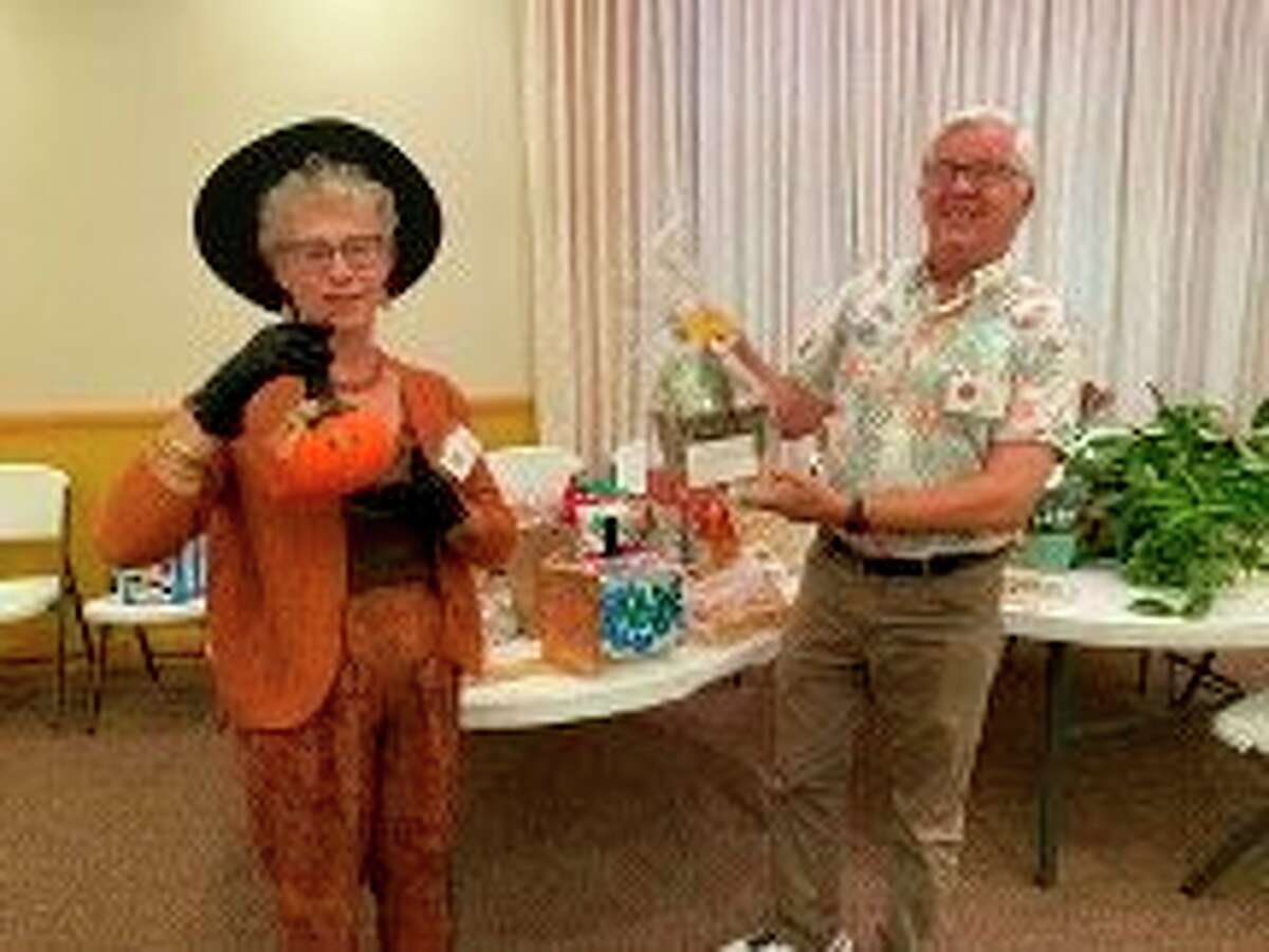 Club members Kathy Stefanski and Mark Schwendner were the auctioneers for theSpirit of the Woods Garden Club auction and potluck dinner on Oct. 11. (Courtesy photo)