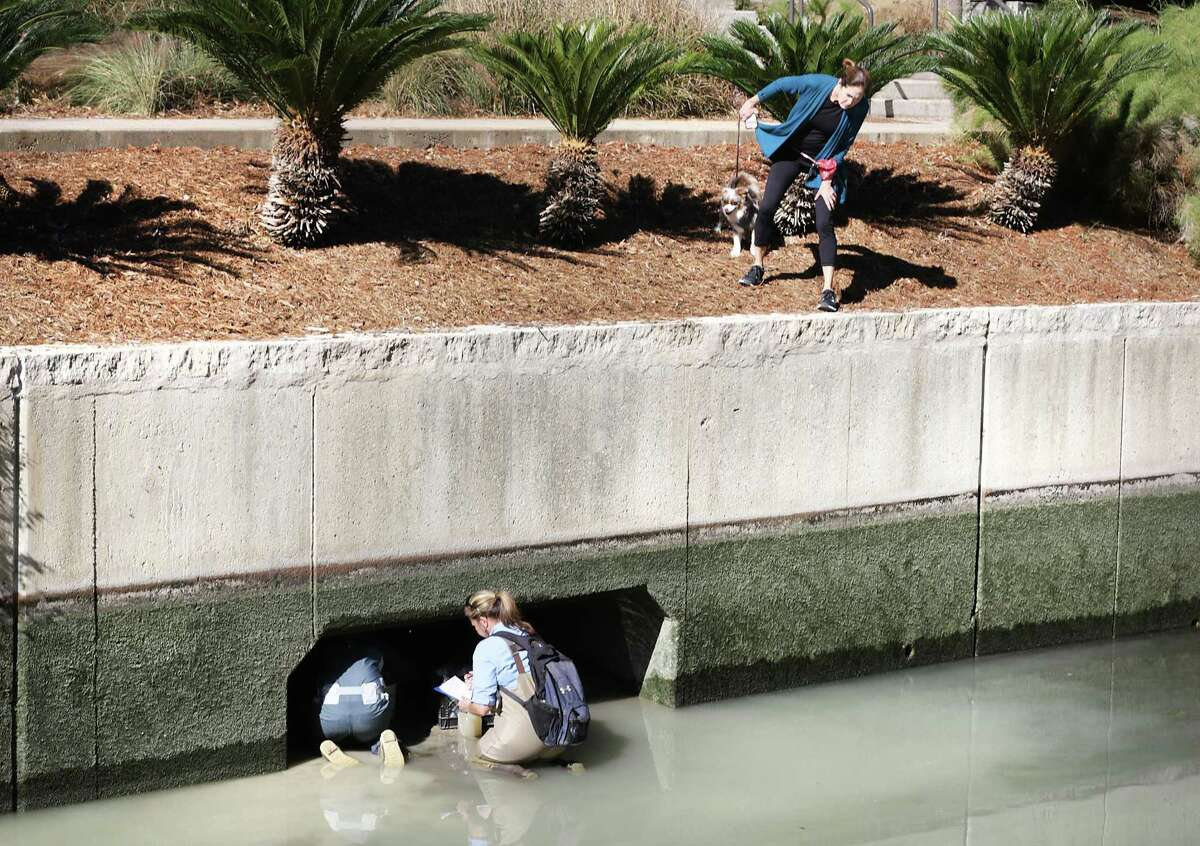 A woman walking her dog along the San Antonio River last year peers over the edge to look at San Antonio River Authority Biologist Karen Sablan, right, and Alicia Ramsey taking water samples as the river is drained for cleaning.