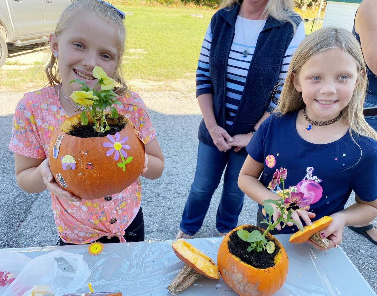 Jozie Skiera and Emmie Skiera proudly show their decorated pumpkins that also house plants inside.