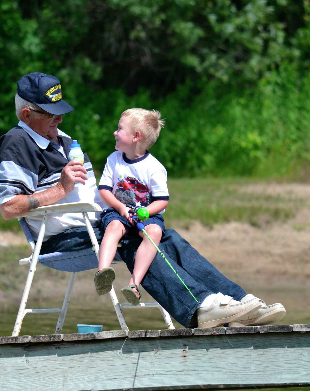 """Steve Griffin won a first-place photography award from the Association of Great Lakes Outdoor Writers for this photo that he entitled """"Great, Grandpa,"""" showing Hope resident Courtney Fillmore and his great-grandson, Nolan Curtis, fishing on a relative's dock. The photo wason the cover of the Summer 2021 issue of Michigan Out-of-Doors magazine.(Steve Griffin)"""