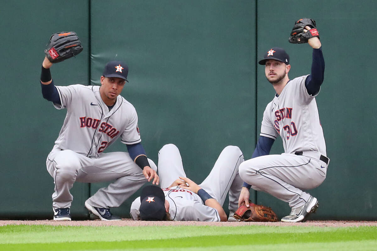 Houston Astros outfielders Michael Brantley, left, and Kyle Tucker (30) call for medical attention for center fielder Jake Meyers after he slammed into the center field wall going after a home run ball hit by Chicago White Sox designated hitter Gavin Sheets during the second inning in Game 4 of the American League Division Series Tuesday, Oct. 12, 2021, in Chicago. Meyers was injured on the play and had to leave the game.