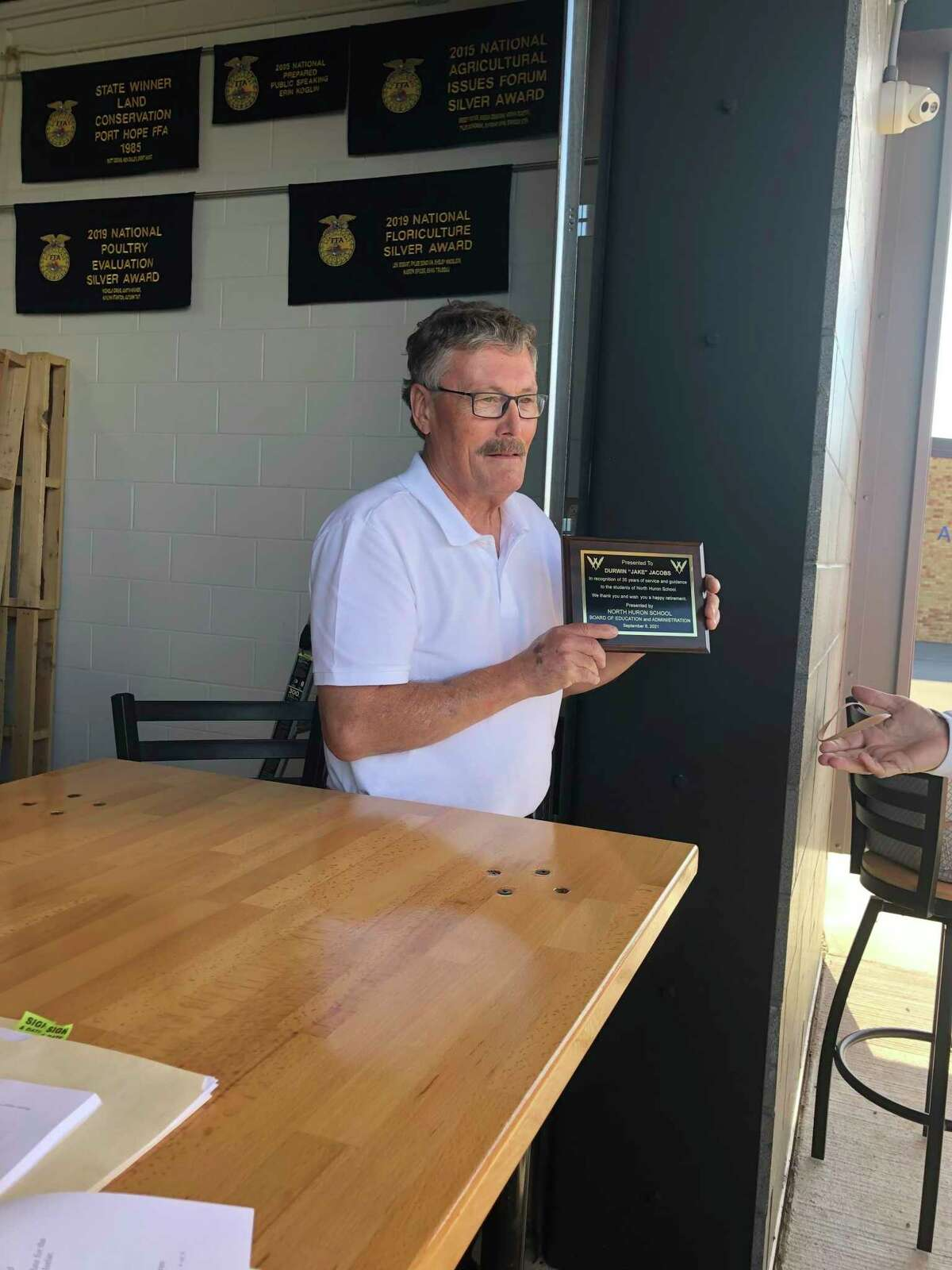 Durwin Jacobs holds a plaque commemorating 35 years of service. (Courtesy Photo)