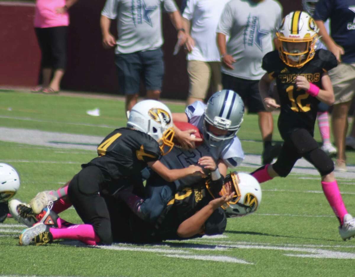 Members of the Deer Park Junior Tigers bring down League City Cowboy Jack Higginbotham, after one of his two interceptions Saturday.