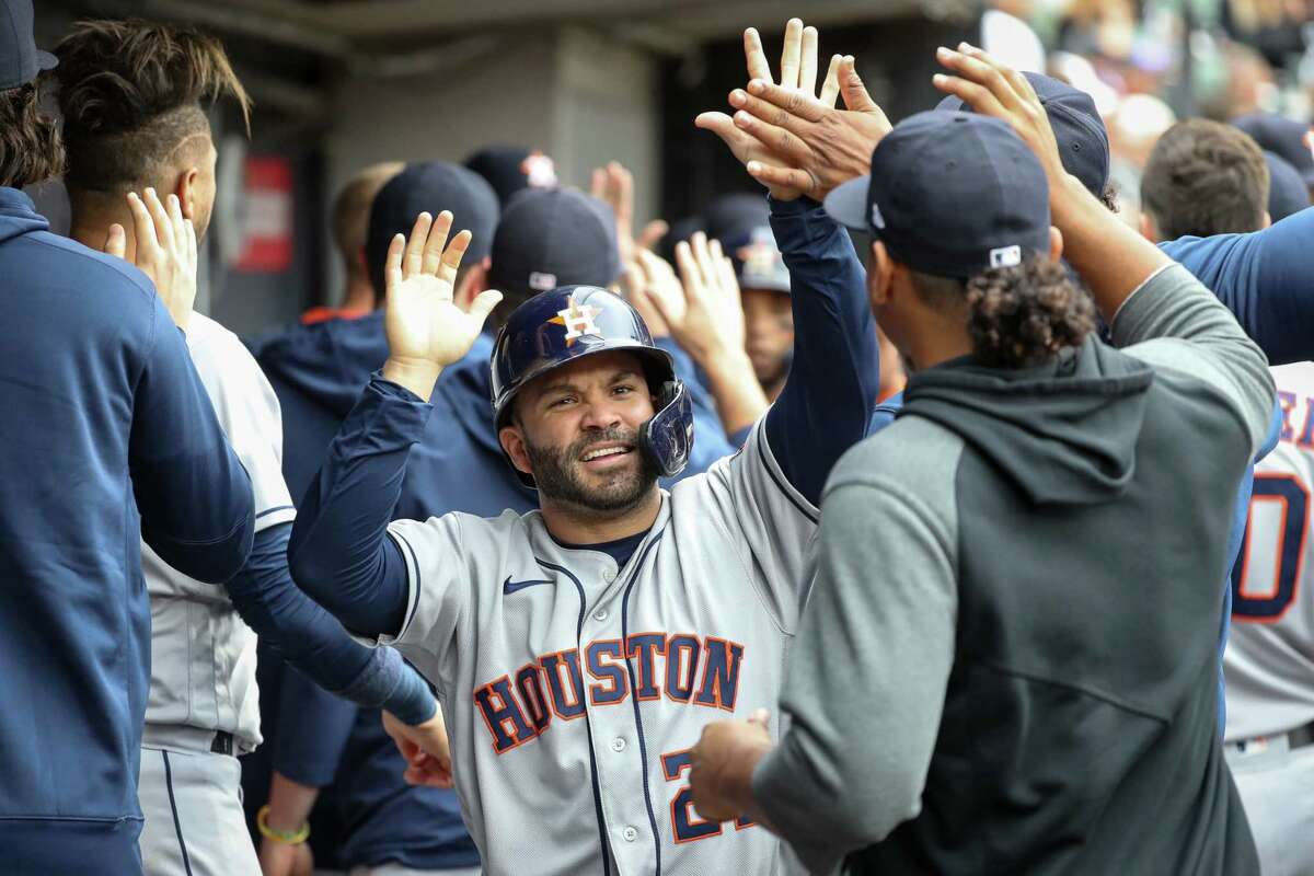 Houston Astros second baseman Jose Altuve (27) high fives his teammates in the dugout after scoring against the Chicago White Sox on an RBI double by Alex Bregman during the fourth inning in Game 4 of the American League Division Series Tuesday, Oct. 12, 2021, in Chicago.