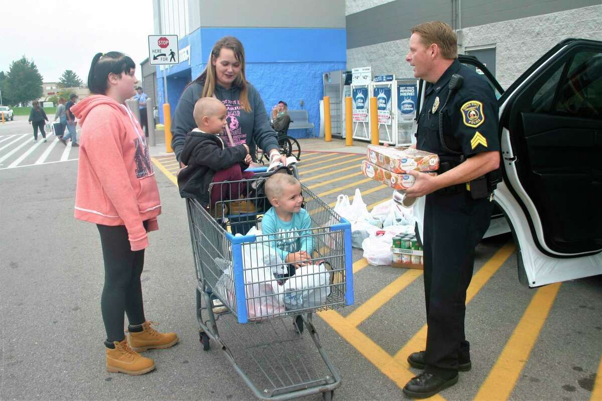 Ferris DPS Sergeant Tim Jacobs accepts food donations from shoppers in the Walmart parking lot during the Faith and Blue food drive for Manna Pantry this weekend. (Pioneer photo/Cathie Crew)