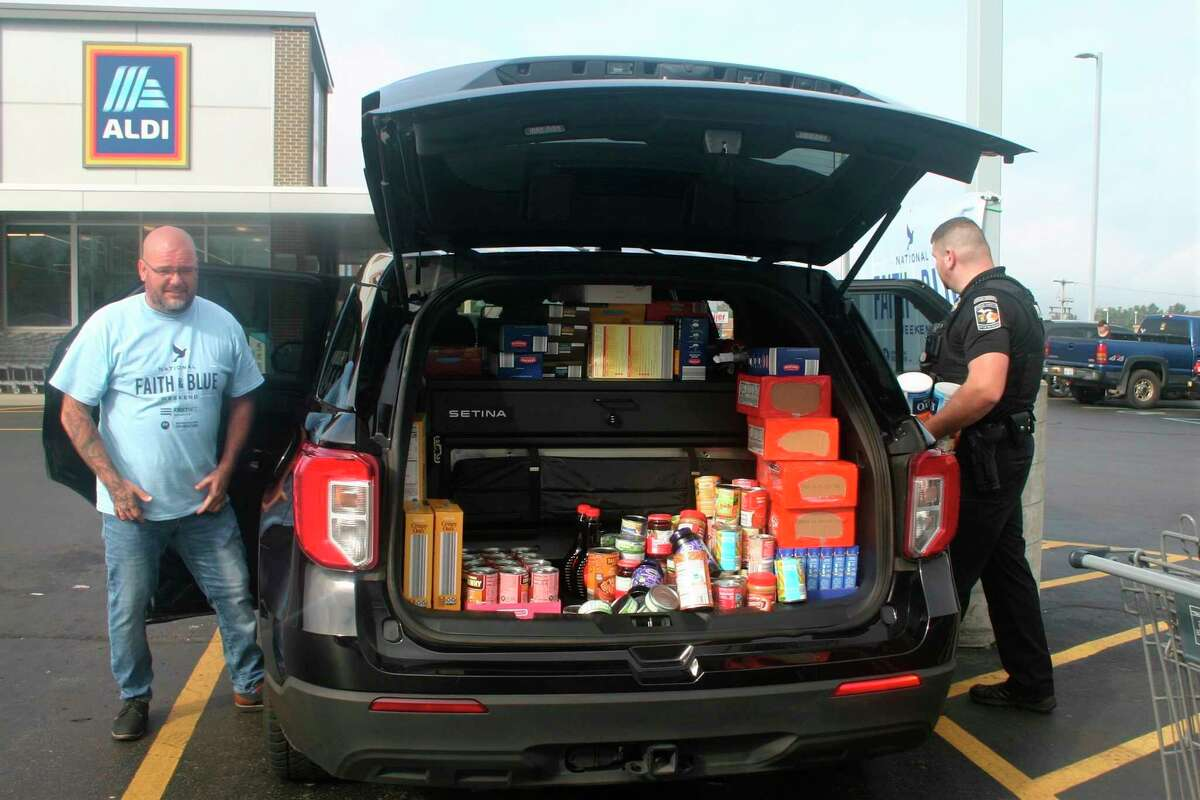 Reverend Jeremy Wicks, with First United Methodist Church, and Officer Thomas Tanner, with BRDPS, collect donated food items in the parking lot of Aldi this weekend as part of the Faith and Blue Weekend food drive for Manna Pantry. (Pioneer photo/Cathie Crew)