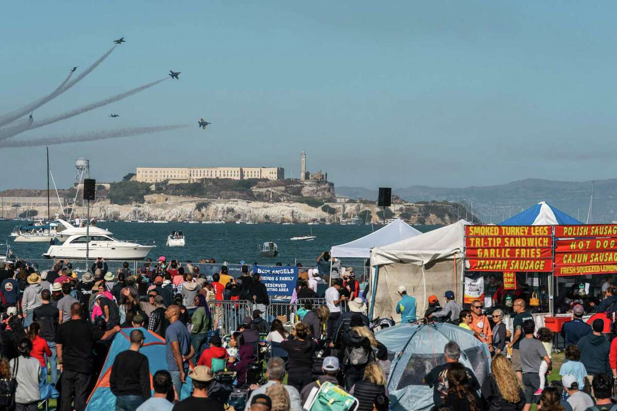The U.S. Navy Blue Angels break formation over Alcatraz Island as spectators at Marina Green watch the Air Show at Fleet Week in San Francisco. The event contributed to a busy weekend as more people used public transit services than any previous time during the pandemic.