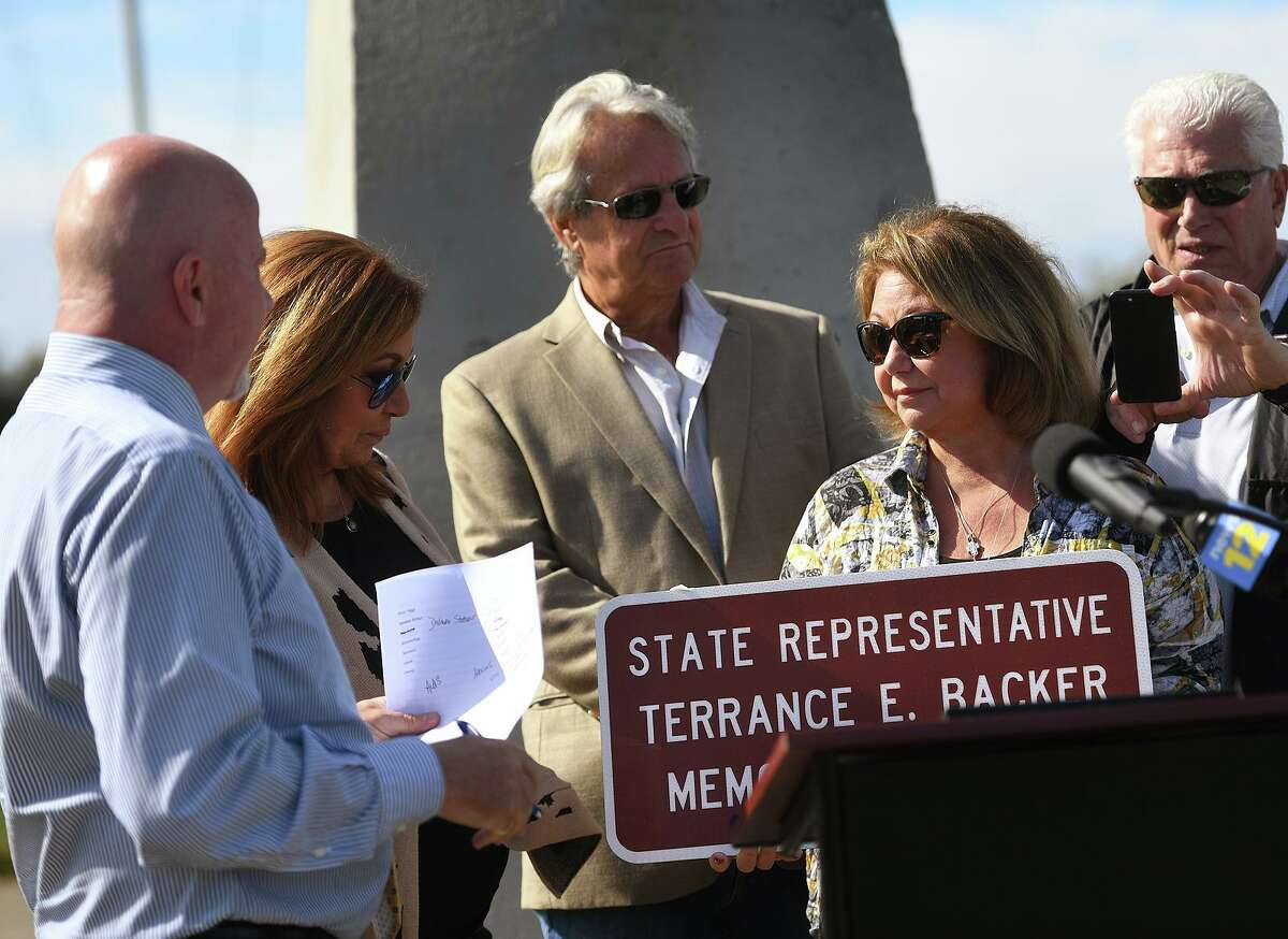 From left; State Rep. Joe Gresko, D-Stratford, presents a sign naming a section of Route 113 after former Stratford Rep. Terry Backer to Backer's sisters Cheryl Backer and Kathleen Patchen in Stratford, Conn. on Tuesday, October 12, 2021. Before serving in Hartford, Backer was the Soundkeeper and a lifelong environmental activist.