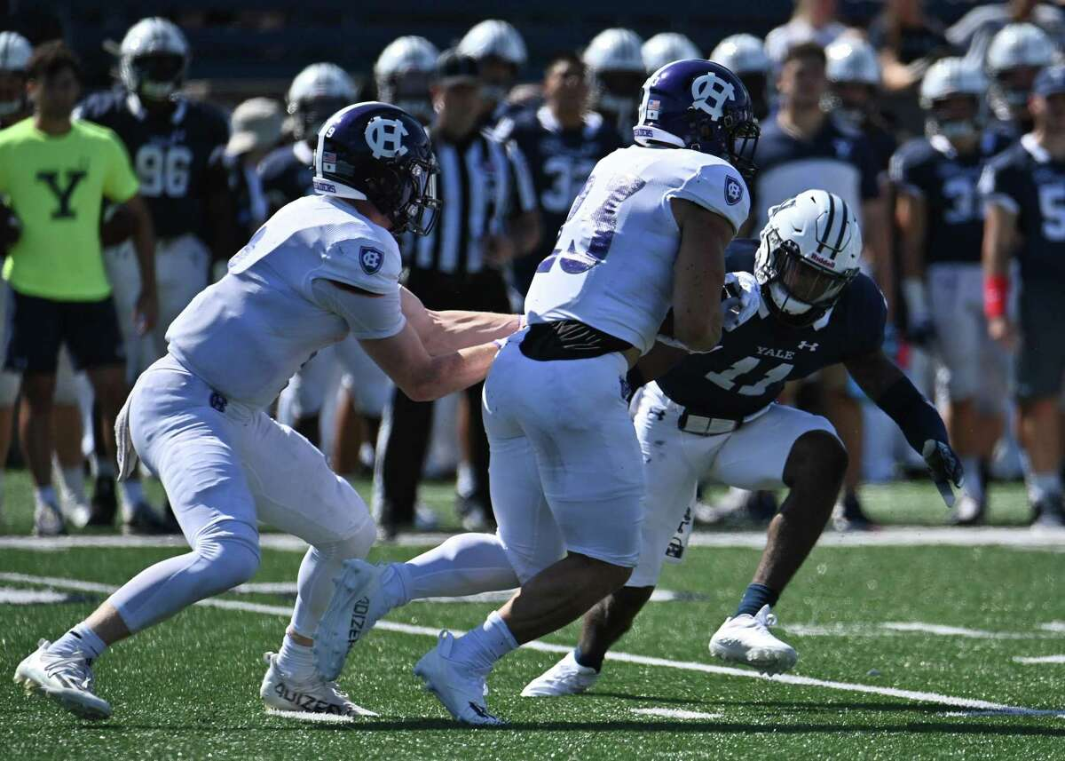 Yale's Dathan Hickey (11) reads the play and makes a quick tackle on Holy Cross' back Jordan Fuller (23) on Sept. 18 at the Yale Bowl in New Haven.
