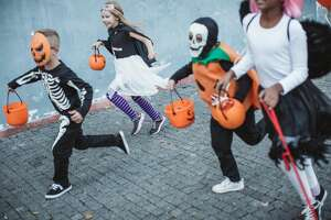 Group of children go trick or treating wearing costumes.