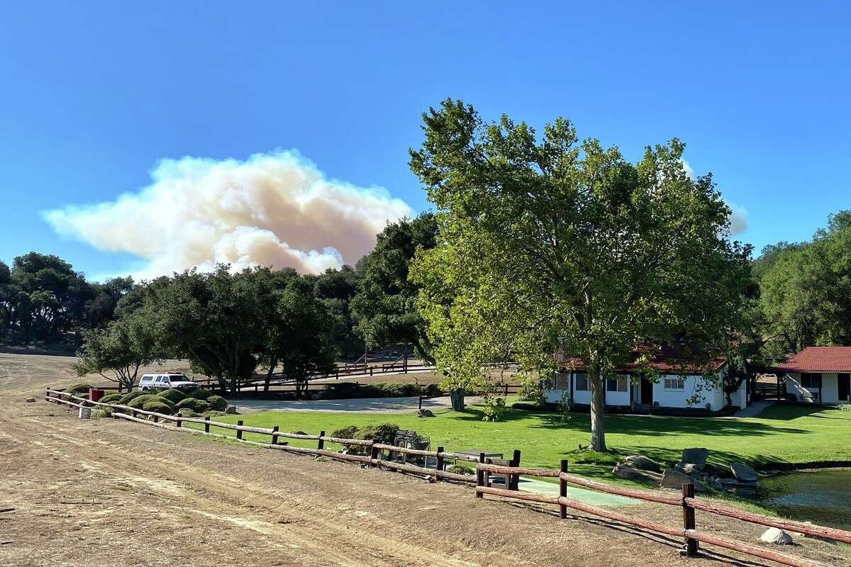 A smoke column builds in the distance behind former President Ronald Reagan's Rancho del Cielo in Santa Barbara County. The Alisal Fire was several miles from the ranch on Oct. 12, 2021.