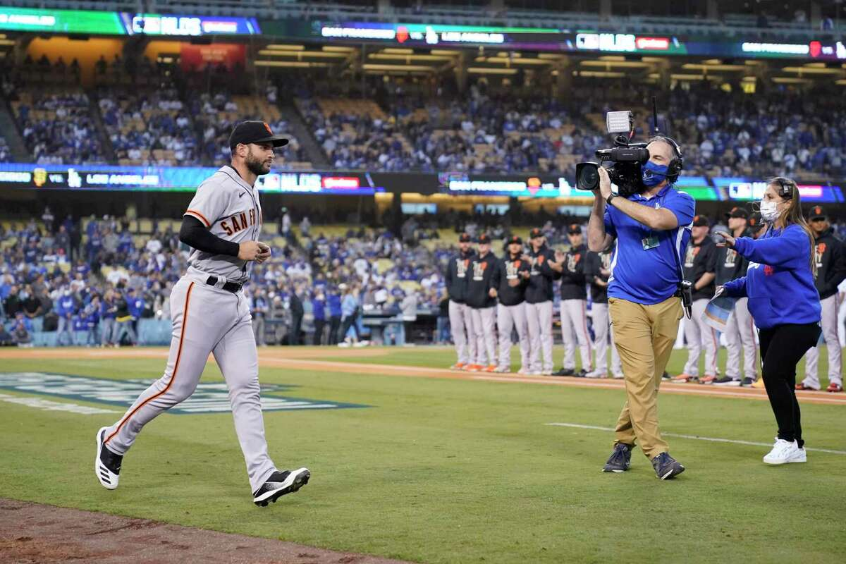 San Francisco Giants second baseman Tommy La Stella, left, is introduced before Game 3 of a baseball National League Division Series against the Los Angeles Dodgers, Monday, Oct. 11, 2021, in Los Angeles. (AP Photo/Ashley Landis)