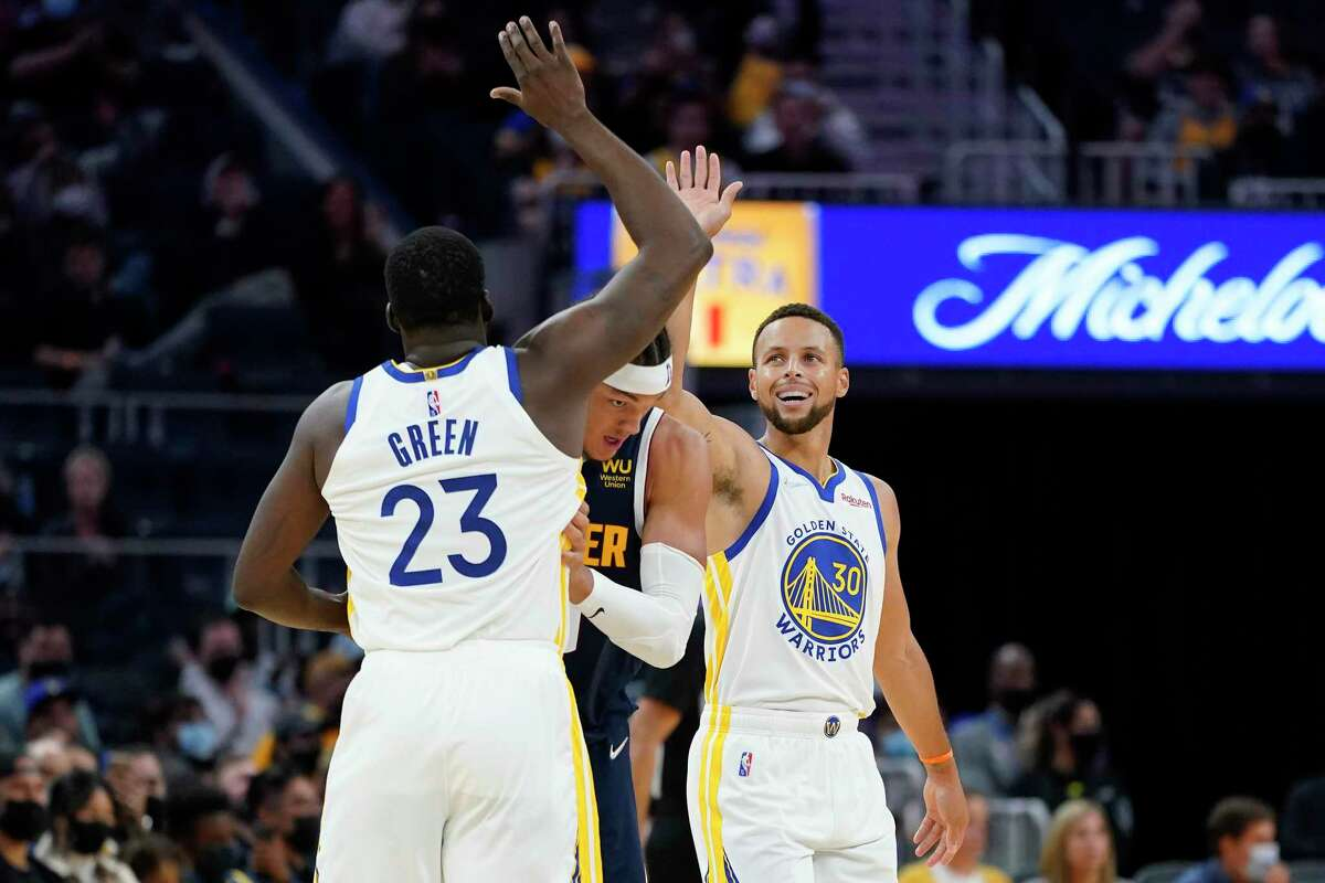 Golden State Warriors forward Draymond Green (23) celebrates with guard Stephen Curry (30) around Denver Nuggets' Aaron Gordon, middle, during the first half of a preseason NBA basketball game in San Francisco, Wednesday, Oct. 6, 2021. (AP Photo/Jeff Chiu)