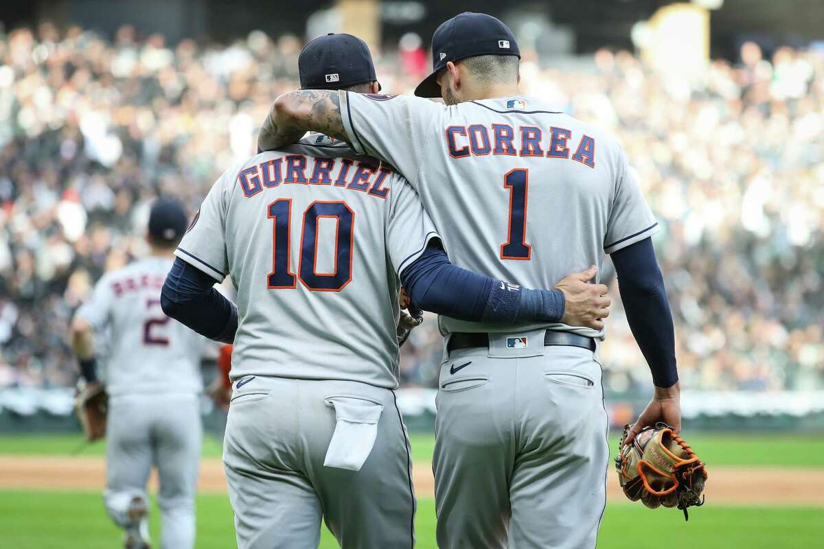Houston Astros first baseman Yuli Gurriel (10) and shortstop Carlos Correa (1) embrace as the walk back to the field to play defense against the Chicago White Sox following the top of the eighth inning in Game 4 of the American League Division Series Tuesday, Oct. 12, 2021, in Chicago.