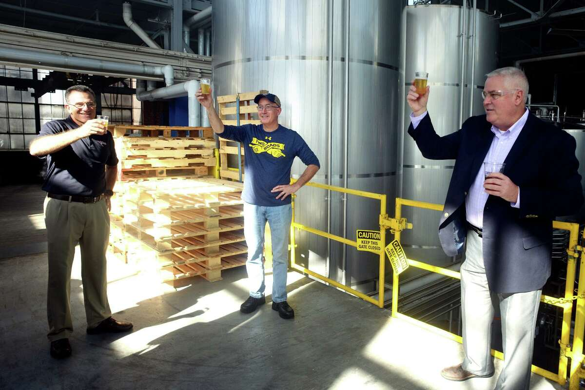Master Brewer Phil Markowski, center, raises a toast as he leads a tour of the Two Roads Brewing Company brewery, in Stratford, Conn. Oct. 12, 2021. Markowski and Two Roads staff were joined by representatives from the University of Connecticut for the introduction of their new TwoConn Ale.