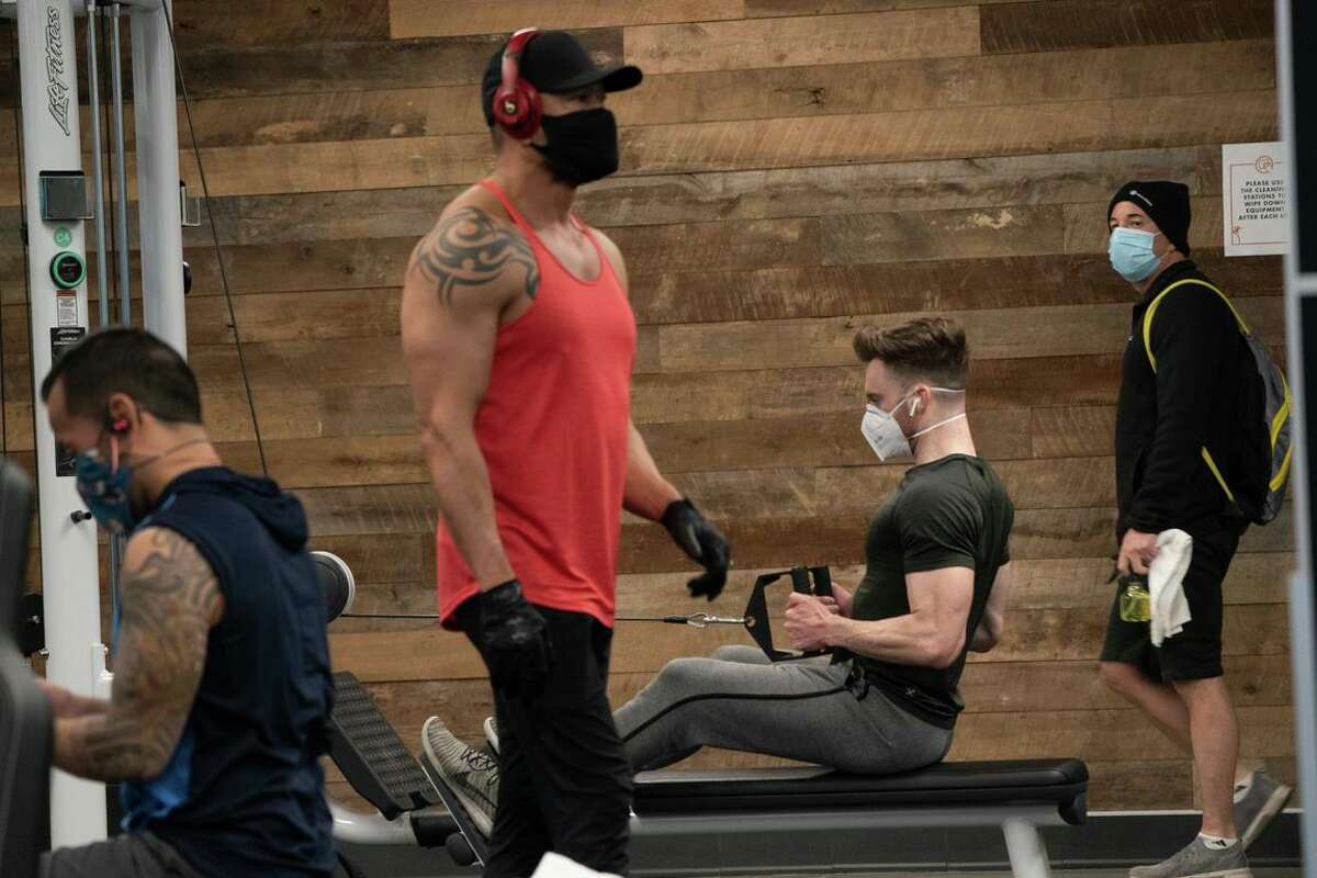 Tino Tuyapala (center) works out at Fitness SF before the most restrictive purple tier shutdown in November. San Francisco and Marin counties are easing mask rules to allow fully vaccinated people to take off their masks in gyms and offices.