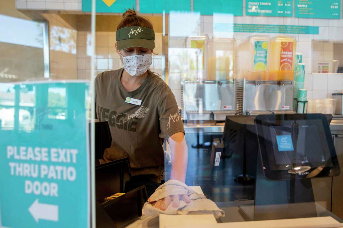A worker wears a mask and gloves while wiping down the register area at Amy's Drive Thru in Corte Madera last September. The new relaxed mask mandates don't include restaurants yet.