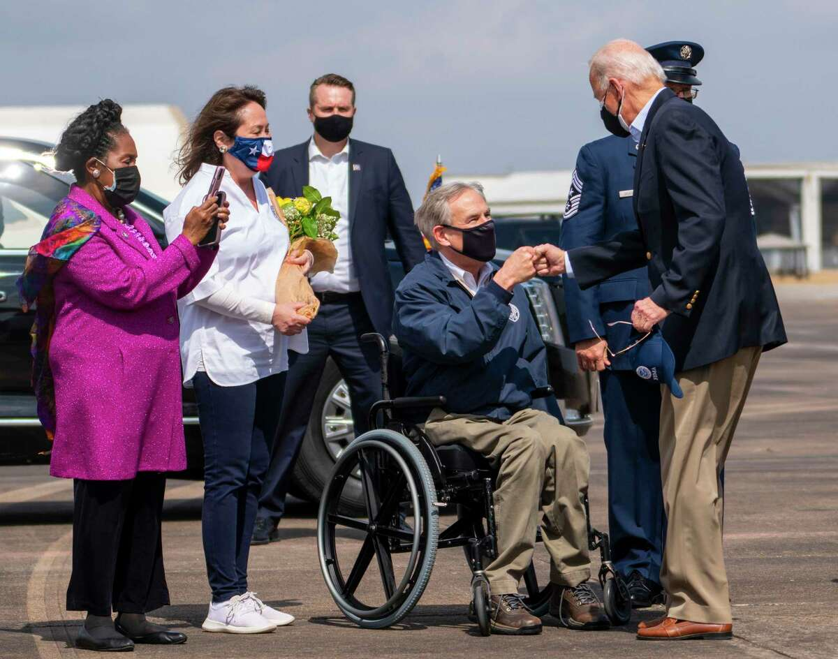 President Joe Biden fist bumps Texas Gov. Greg Abbott upon arrival at Ellington Field Joint Reserve Base in Houston on Friday, Feb. 26, 2021. President Biden and first lady Jill Biden traveled to Houston where they plan to visit with food bank volunteers and President Biden also plans to speak at a COVID-19 vaccination center. (Doug Mills/The New York Times)