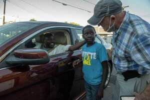 Tim Doherty, right, talks to Sefadine Nour, from Sudan and his son Ismail, 10, outside the West Hill Refugee Welcome Center on Tuesday, Oct, 12, 2021 in Albany, N.Y.