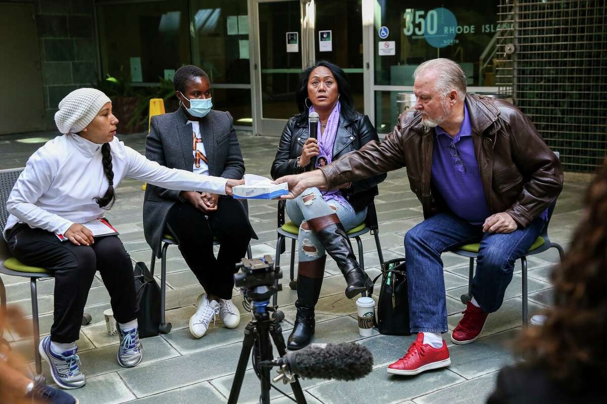 Norma Marquez, left, hands a box of tissues to Alan Hinman, right, while listening to Jenifer Redmond share her story about the murder of her 19-year-old daughter, Sarayah Redmond, in meeting with survivors of violent crimes at the San Francisco District Attorney's Office in San Francisco, Calif. on Tuesday, Oct. 12, 2021. The meeting was held by the city's District Attorney Chesa Boudin, Contra Costa District Attorney Diana Becton and San Joaquin County District Attorney Tori Salazar in order to understand more about survivors' experiences with the criminal justice system and how the system can better serve their needs.