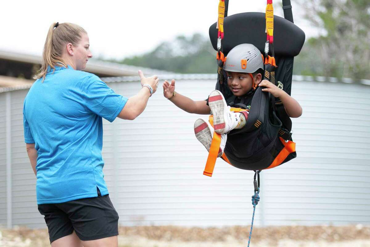Brooke Matula tells 7-year-old Devyn Harrigan that he did a good job testing out a swing on the Fort Challenge section of the new Morgan's Wonderland Camp in San Antonio on Tuesday. The 102-acre, $34 million campground features a zip line and challenge course, a nature center, sports pavilion, concrete bicycle trails and more.