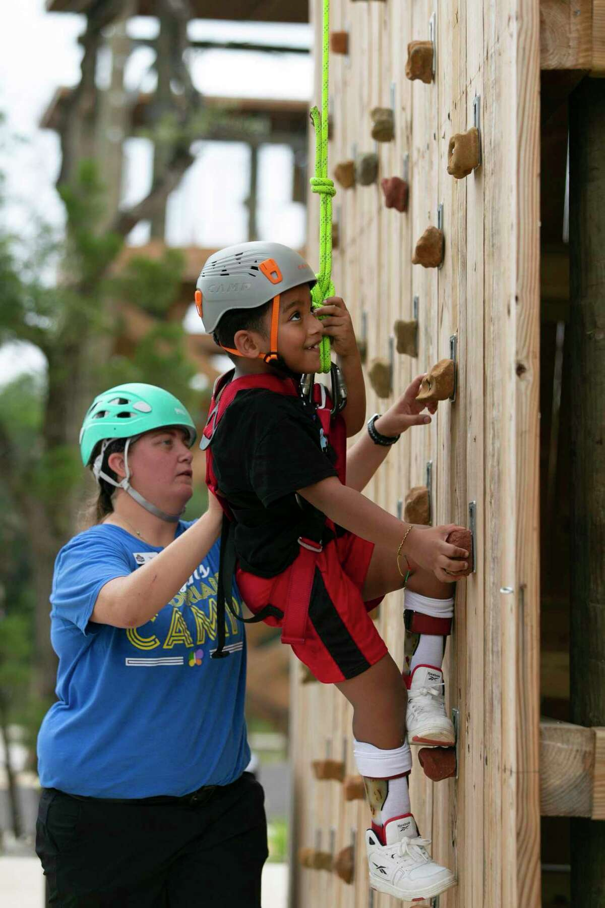 """Torye Gleitz assists 7-year-old Devyn Harrigan as he climbs up the rock wall on the Fort Challenge course inside Morgan's Wonderland Campground, located on the northern outskirts of San Antonio, on Tuesday. The campground was designed by Gordon and Maggie Hartman to be """"ultra-inclusive"""" and accessible to people with special needs."""