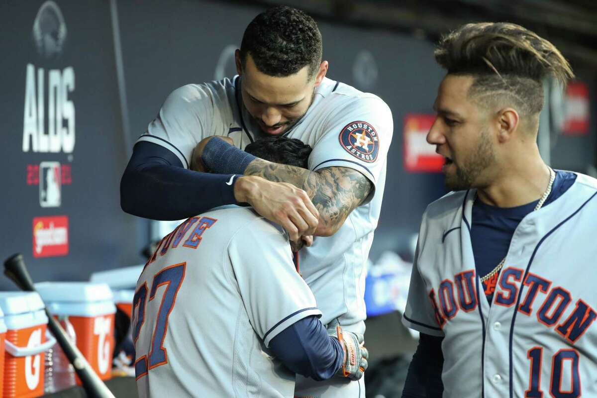 Houston Astros shortstop Carlos Correa (1) embraces Jose Altuve after Altuve hit a solo home run off Chicago White Sox reliever Liam Hendriks during the ninth inning, to cap off a 10-1 win in Game 4 of the American League Division Series to advance to the AL Championship Series, Tuesday, Oct. 12, 2021, in Chicago. It was Altuve's 19th post-season home run, tying former teammate George Springer for the most in franchise history.
