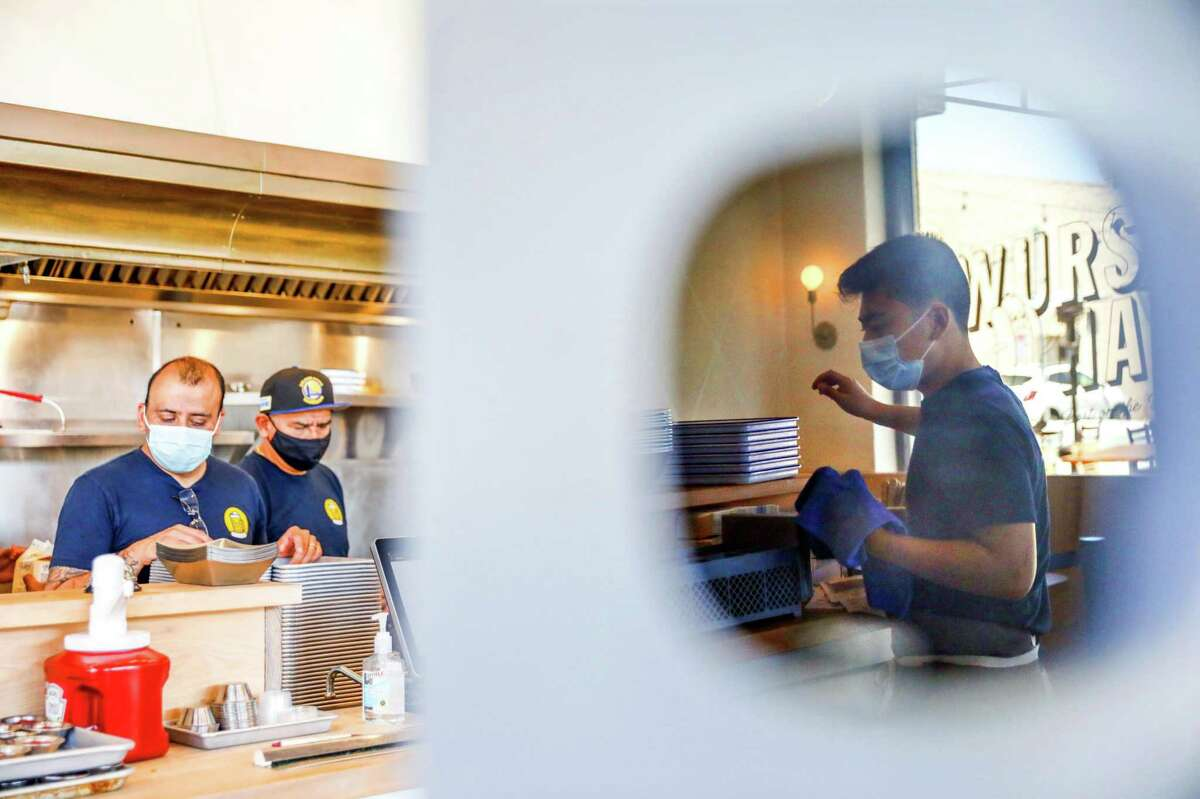 Server Brett Kuwahara (right) wears a mask as he sorts silverware while cooks Orlando Gonzalez (left) and Carlos Gonzalez (center) work at Wursthall in San Mateo, Calif.