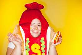 Woman in a hot dog costume holding a hot dog. Taken with a Canon 5D Mark 11 using a ring flash.