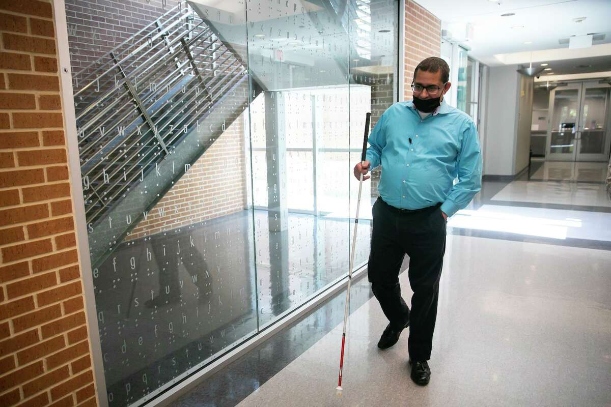 Craig Tallent walks through the lobby at Lighthouse of Houston on Friday. The University of Houston has collaborated with Lighthouse to staff its maintenance call center with employees who are visually impaired.