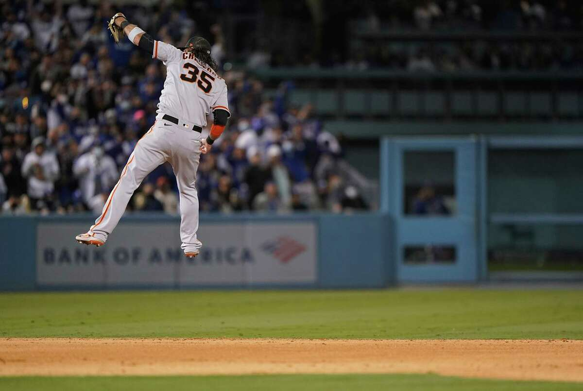 Giants shortstop Brandon Crawford leaps up to rob Mookie Betts of a base hit with two outs in the bottom of the seventh inning of game 3 of the NLDS at Chavez Ravine in Los Angeles, Calif. on Monday, October 11, 2021.